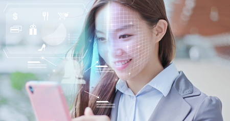 Photo for A business woman is shopping on smart phone with scanning facial recognition. - Royalty Free Image