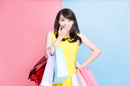 Foto de woman feel surprise and take shopping bag happily on the blue and pink background - Imagen libre de derechos