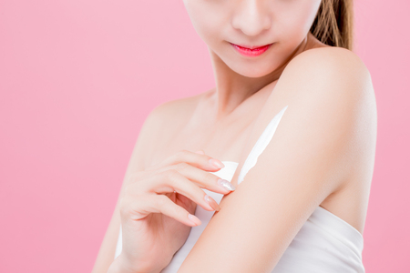 Photo pour beauty woman use cream with arm isolated on pink background - image libre de droit