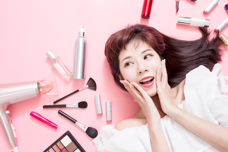 Foto de Young beautiful woman smile and look somewhere with her cosmetic makeup tools - she is lying on the pink floor - Imagen libre de derechos
