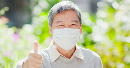 Foto de old man smile show thumb up and wear mask with nature green background - Imagen libre de derechos