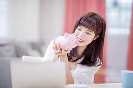 Happy woman look her pink piggy bank and feel happy at home