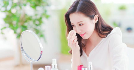 Photo pour Beautiful asian woman using cosmetic sponge on face and look mirror at home - image libre de droit