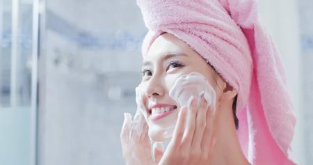 Photo pour woman wash her face in the bathroom after shower - image libre de droit