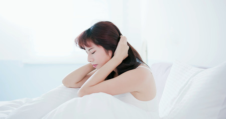 Foto de Young woman has a trouble sleeping and feel unhappy in the morning - Imagen libre de derechos