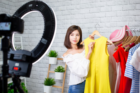 Foto de beauty female fashion vlogger presenting yellow dress to camera and smiling showing clothes selling online live streaming - Imagen libre de derechos