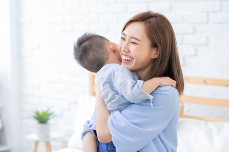 Foto de happy family with child boy hug mother at home - Imagen libre de derechos