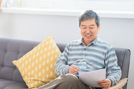 old asian man look somrthing by magnifier at home
