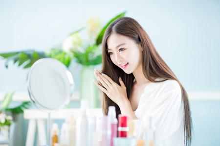 Photo pour Beautiful asian woman touch her health long straight hair care with mirror at home - image libre de droit