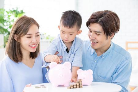 Photo pour Family saving money and putting coins into piggy bank - image libre de droit