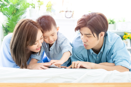 Foto de Happiness asian family - Parent read book with child happily at home - Imagen libre de derechos