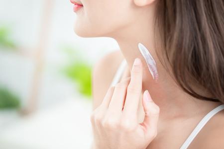 Photo pour young woman applying cream or sunscreen on her neck - image libre de droit