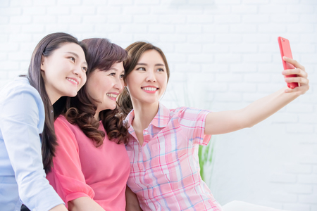 Photo pour Daughters and mom take selfie together happily - image libre de droit