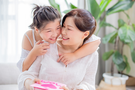 Foto für Happy mother day - daughter give card and gift to her mom at home - Lizenzfreies Bild