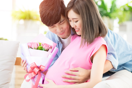 Photo pour Happy mother day - sweet man send flower to his wife which is pregnant - image libre de droit