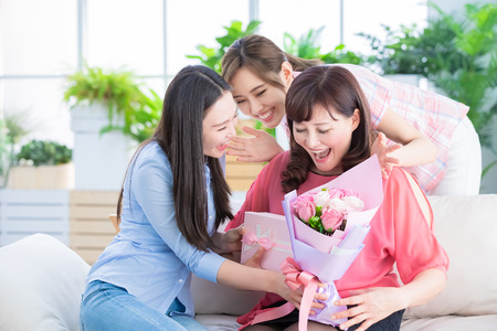 Photo pour two daughters give gifts to her mom and celebrate happy mother day at home - image libre de droit