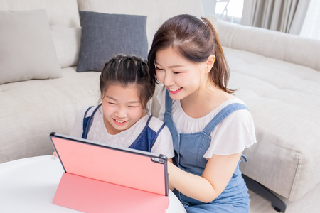 Foto de Mom and daughter use tablet happily at home - Imagen libre de derechos