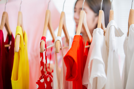 Photo pour young woman choosing clothes on a rack at home or in store - image libre de droit