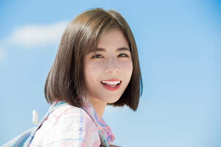 Foto per asian student tavel and smile to you with sky background - Immagine Royalty Free