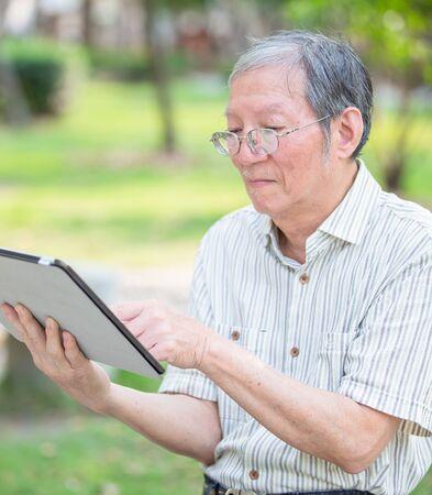 Foto de Older man use tablet in the park - Imagen libre de derechos