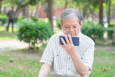 Photo pour Older man take off the glasses and watch video by cellphone in the park - image libre de droit