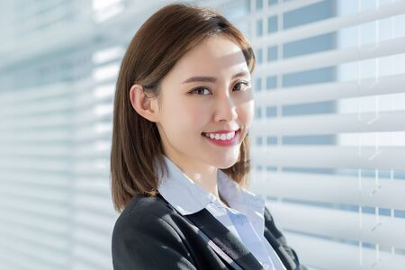 Photo pour Asian business woman smile at you with confidence by the curtain in the office - image libre de droit
