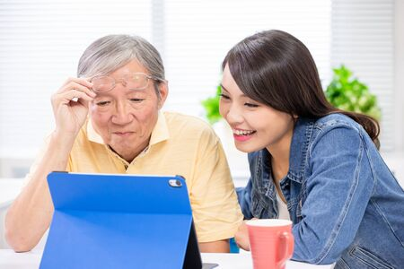 Photo for Young daughter teach elder father use tablet pc at home - Royalty Free Image