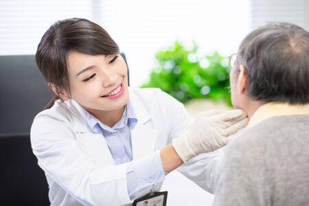 Photo pour Female doctor check throat for elder patient carefully - image libre de droit