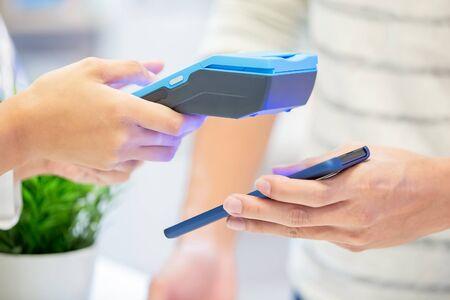 Foto de mobile payment concept - close up of pay bills by Phone to Credit Card System - Imagen libre de derechos