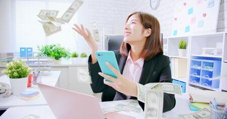 Photo pour asian business woman excited with raining money - image libre de droit