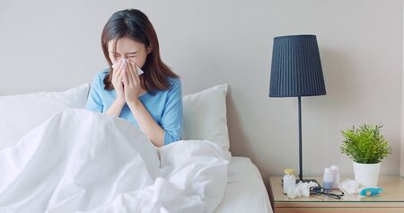 Photo for asian woman sick and sneeze with tissue paper in the bedroom - Royalty Free Image