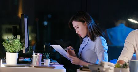 Foto de asian businessman and businesswoman overtime work and read the documents in the office - Imagen libre de derechos