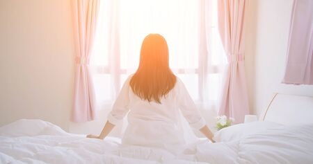 Foto de back view of woman sit on bed and look out windows after wake up in the morning at home - Imagen libre de derechos