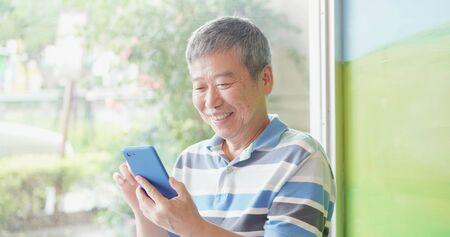 Photo pour asian elder man use smart phone beside windows - image libre de droit