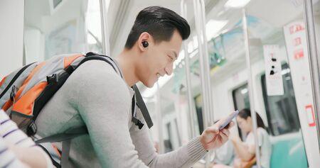 Foto de asian man use wireless earbuds to watch video on the subway - Imagen libre de derechos