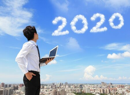 Photo pour Young business man using laptop and look to 2020 year text with blue sky - image libre de droit
