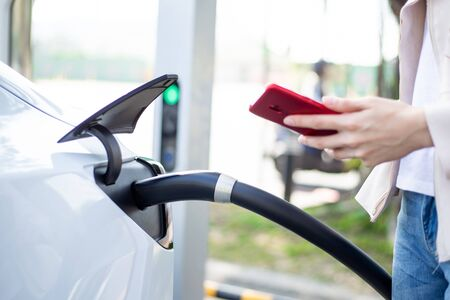 Photo for Close up of woman use smart phone while waiting and power supply connect to electric vehicles for charging the battery in car - Royalty Free Image