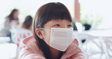 Photo pour children with protective mask because of transmissible infectious diseases indoor in the crowd - image libre de droit