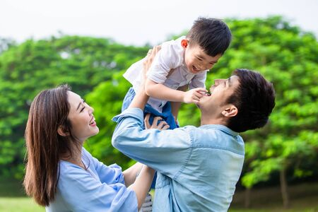 Photo for Father hold boy in his arm and parents play with kid outdoor - Royalty Free Image