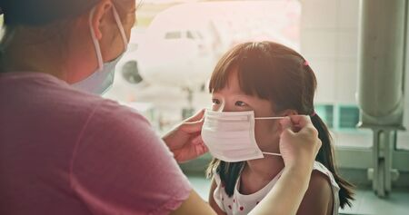 Photo pour Asian parents wear masks to their children because of transmissible infectious diseases indoor in the airport - image libre de droit