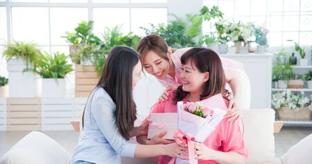 Foto de two daughters give flowers to her mom and celebrate happy mother day at home - Imagen libre de derechos