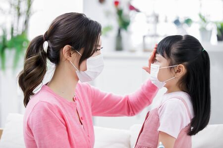 Photo pour Mom touch kids forehead to check her fever condition at home - image libre de droit