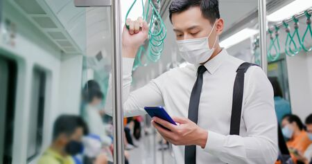 Photo pour Asian business man with surgical mask face protection use a smartphone  and keep social distancing to crowd while commuting in the metro or train - image libre de droit