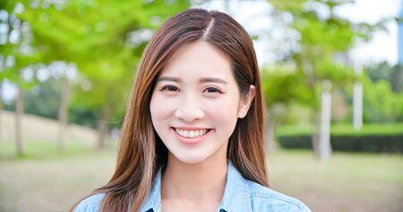 Photo pour Asian young woman smile to you outdoor - image libre de droit