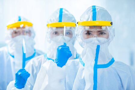 Foto de doctors look to you with fist gesture - they wear the isolation gown or protective suits and surgical face masks in the control area to prevent the spread of coronavirus - Imagen libre de derechos