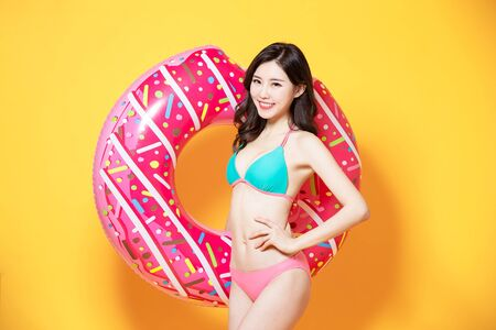 Foto de asian woman is relaxed and carefree and ready to travel wearing bikini swimsuit with donut swim ring - Imagen libre de derechos