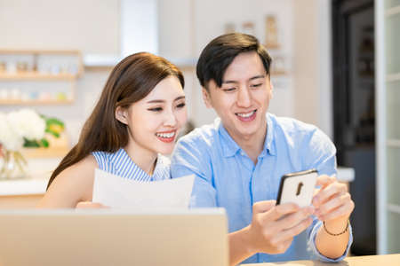 Photo for asian couple looking some information on the internet together by digital tablet at home happily - Royalty Free Image