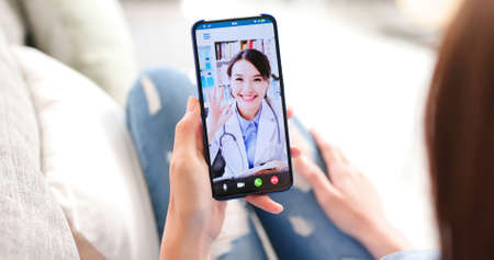 Foto de Telemedicine concept-back view of asian woman has video chat with female doctor and she make a discussion with ok gesture - Imagen libre de derechos