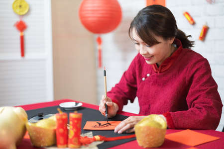Foto de asian female writing spring festival couplets is celebrating Chinese holidays with word meaning new year and may wealth come generously to you - Imagen libre de derechos