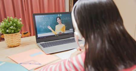Photo pour rear view of asian girl is learning math and looking elementary school female teacher teaching online through laptop at home - image libre de droit